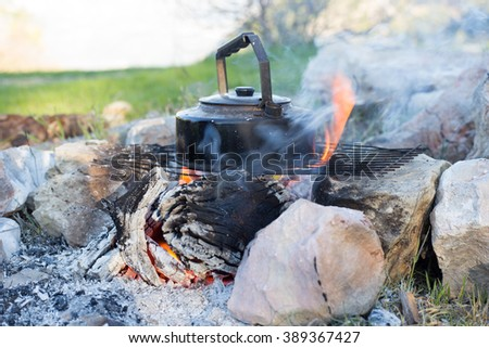 Kettle on the fire. Making coffee in a hike in the woods - stock photo