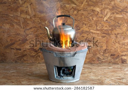 Kettle on the fireplace, on wooden background - stock photo