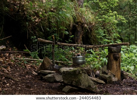 Kettle over campfire  - stock photo
