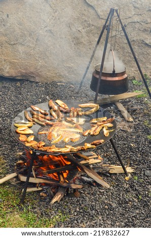 Kettle over the fire and roaster full of Porcini wild mushrooms fried in deep oil - stock photo