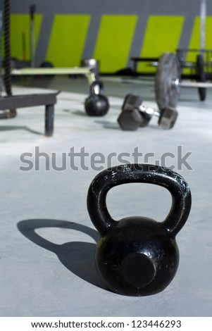 Kettlebell at fitness gym with lifting bars in background - stock photo