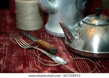 Kettles, fork, knife on old wooden table. - stock photo