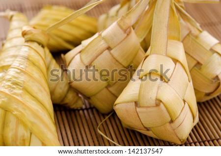 Ketupat or packed rice dumpling. Delicious traditional Malay ramadan food. Popular Malaysian food on bamboo mat. - stock photo