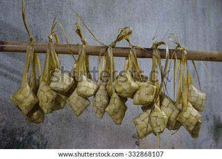 Ketupat (Rice Dumpling) hanging on bamboo. Ketupat is a natural rice casing made from young coconut leaves for cooking rice during eid Mubarak. - stock photo