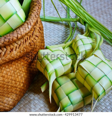 Ketupat (rice dumpling) on a traditional mat which is a local delicacy during the festive season in South East Asia. Ketupat, a natural rice casing made from young coconut leaves for cooking rice. - stock photo