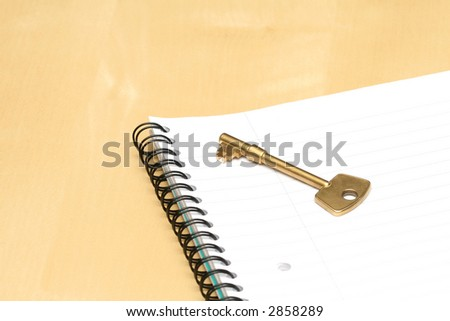 Key and notebook on a table - stock photo