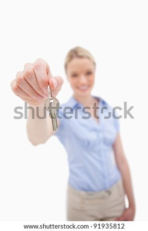 Key being handed over by woman against a white background - stock photo