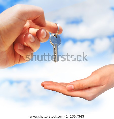 Key in hand over blue sky background. - stock photo