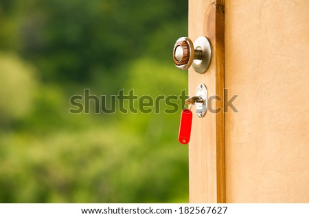 Key in keyhole of country house - stock photo