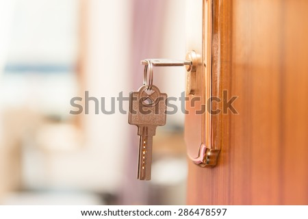 Key in keyhole on door - stock photo