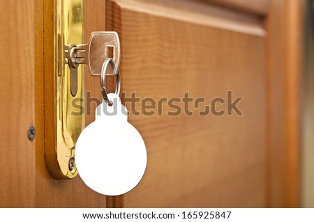 key in keyhole with blank label shape Christmas ball - stock photo