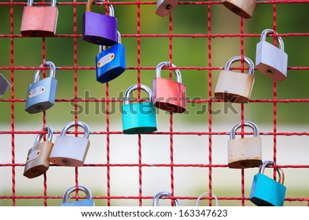 key lock on steel net fence with shallow depth of field - stock photo