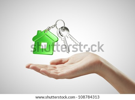 key with  green key chain in hand on white background - stock photo