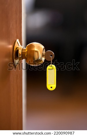 Key with tag sticking in the door closeup - stock photo