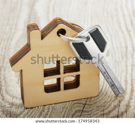 Key with wooden house on desk - stock photo