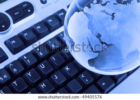keyboard and glass earth globe - focus on globe - stock photo