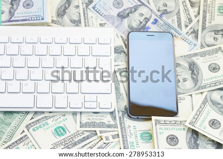 keyboard and modern smart phone  on money background - stock photo