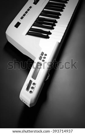 Keyboard of synthesizer on black background - stock photo