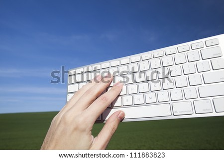 Keyboard on blue sky with hand - stock photo