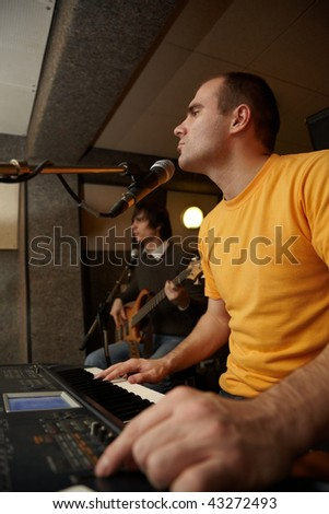keyboarder is playing near microphone. guitar player in out of focus - stock photo