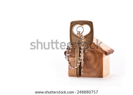 Keychain house is made of olive wood with a key on a white background - stock photo