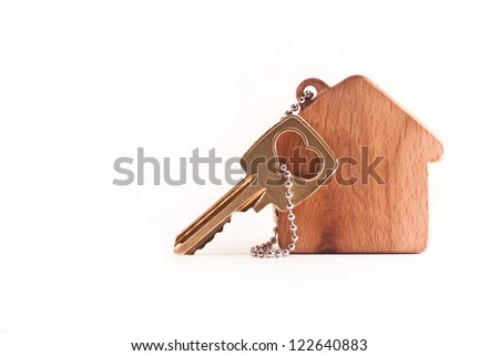 Keychain in the shape of a tree house with a key on a white background - stock photo