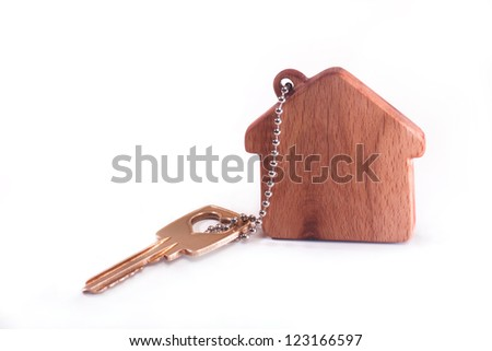 Keychain in the shape of the house with a key - stock photo