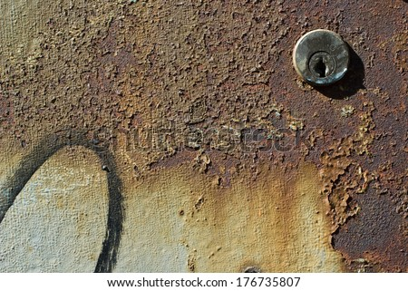 Keyhole in a rusted metal plate - stock photo