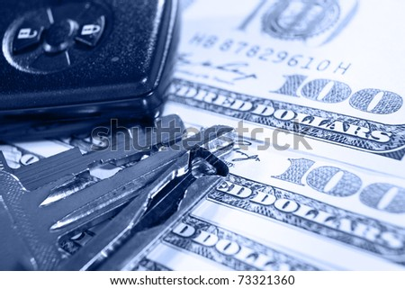 Keys and alarm device on top of several one hundred dollar bills - stock photo