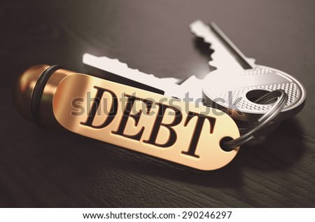Keys and Golden Keyring with the Word Debt over Black Wooden Table with Blur Effect. Toned Image. - stock photo
