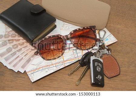 Keys and sunglasses on a road map with wallet,Ready to travel - stock photo