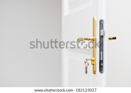 Keys in the keyhole with beautiful golden doorknob on white door - stock photo
