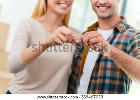 Keys of their new apartment. Cropped image of young loving couple holding keys and smiling while standing in their new house - stock photo