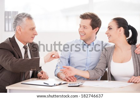 Keys to your new home! Young couple sitting together at the table while senior man in formalwear giving a key to them and smiling - stock photo