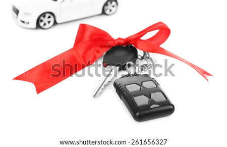 Keys with red bow and car as present isolated on white - stock photo