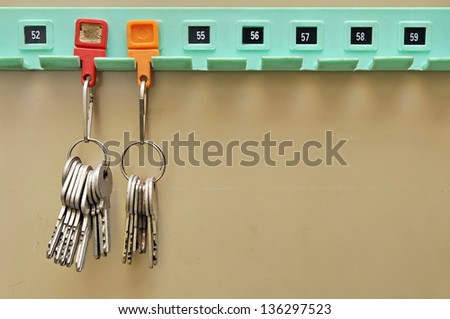 Keys with tags hanging on a wooden board - stock photo