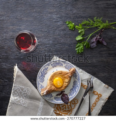 Khachapuri on plate with herbs. Top view - stock photo