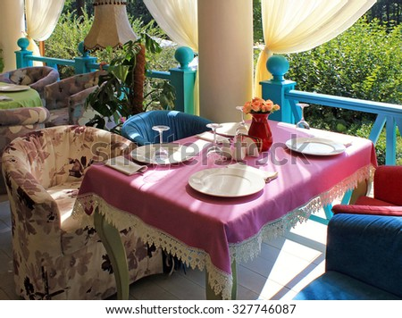 KHARKOV, UKRAINE - AUGUST 12, 2015: Beautiful terrace with bright colored armchairs and table clothes in country restaurant , Kharkov, Ukraine - stock photo
