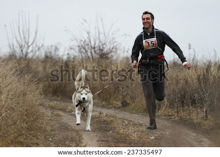 Kharkov, UKRAINE -?? November 15, 2014: Oleg Rudak at canicross heats during Men's 3100 m at Sled dogs dry land race Autumn Cup - 2014 - stock photo