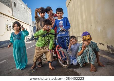 KHASAB (MUSANDAM), OMAN - DECEMBER 27: Small unidentified children in Khasab street on December 27, 2015. On Musandam peninsula lives combination  of Omani, Iranians and other nations of Persian Gulf. - stock photo
