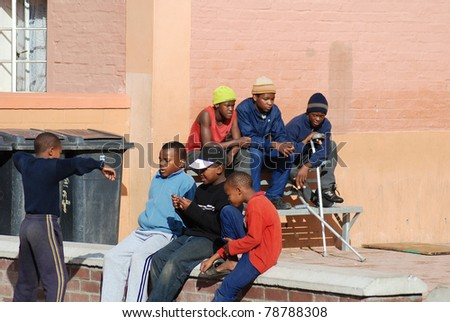 KHAYELITSHA, CAPE TOWN - MAY 22 : A unidentified group of young teenagers sit on the side of a street in Khayelitsha township, the name is Xhosa for New Home, on May 22, 2007, Cape Town, South Africa - stock photo