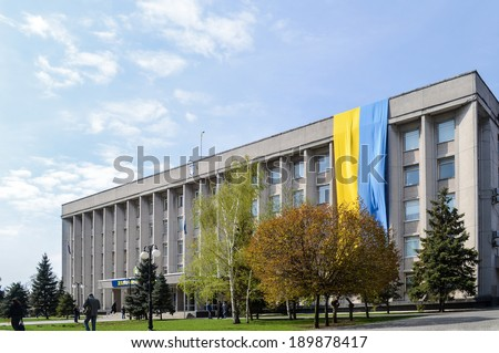 KHERSON, UKRAINE - APRIL 15, 2014: large Ukrainian flag on the city hall of Kherson in the Southern part of Ukraine for integrity of Ukraine against Russian aggressive  attempts to split the country. - stock photo