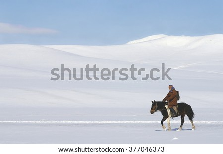 KHUSTAIN NURUU , MONGOLIA - 02-05-2008 ; Mongolian woman in wintertime is riding her horse in a beautiful snow landscape - stock photo