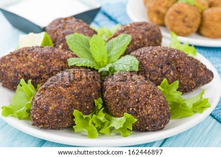 Kibbeh - Middle Eastern minced meat and bulghur wheat fried snack. Also popular party dish in Brazil (kibe). Falafel and tzatziki dip on background. - stock photo
