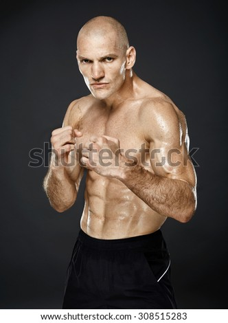 Kickbox fighter posing shirtless and with bare knuckles in guard stance on gray background - stock photo