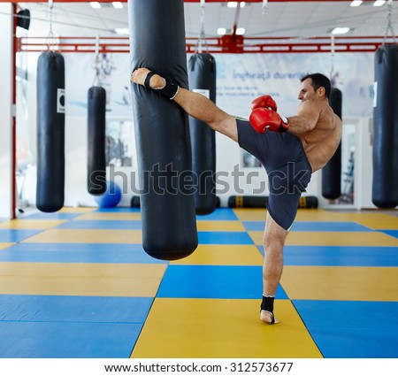 Kickbox fighter training in the gym with the punch bag - stock photo