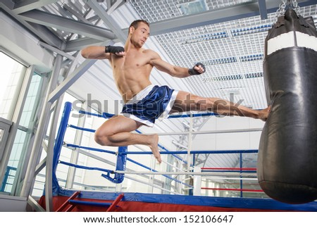 Kickboxer. Confident young kickboxer training at the punching bag - stock photo