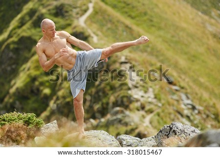 Kickboxer or muay thai fighter practicing shadow boxing on a mountain  - stock photo