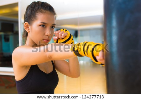 Kickboxing girl practicing with a punching bag - stock photo