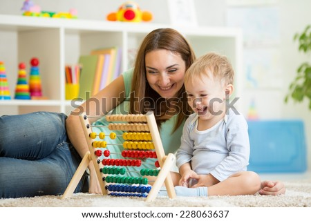 kid and his mother playing with abacus - stock photo